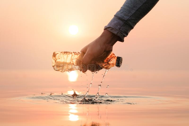 Женщина руки комплектуя вверх пустое пластиковой чистки бутылки на пляже, добровольной концепции загрязнение фото кризиса экологи стоковое изображение rf