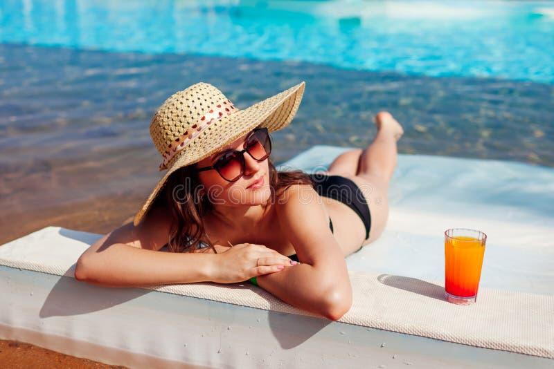 Женщина ослабляя в бассейне гостиницы лежа на шезлонге с коктейлем каникула территории лета katya krasnodar Совсем включительно стоковое фото