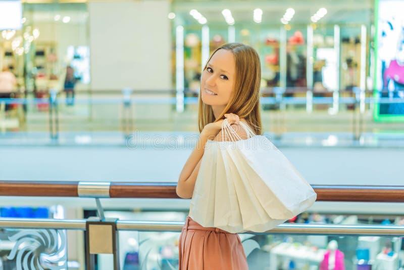 Женщины нося много хозяйственные сумки в запачканном торговом центре стоковое изображение rf