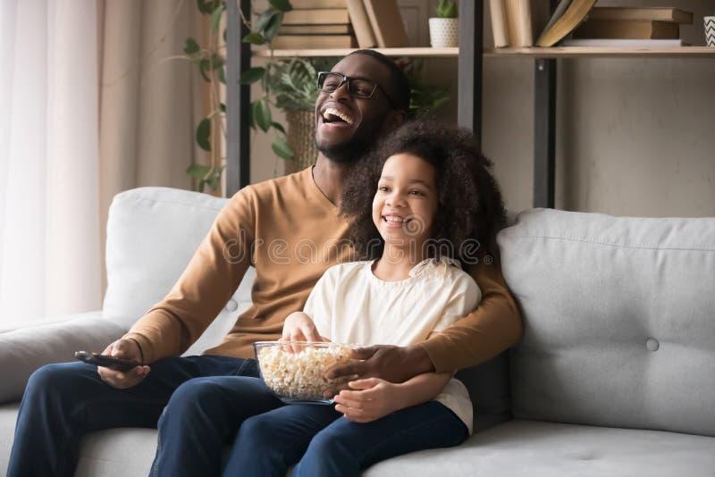 Жизнерадостная Афро-американская девушка отца и ребенка смеясь смотрящ ТВ стоковая фотография