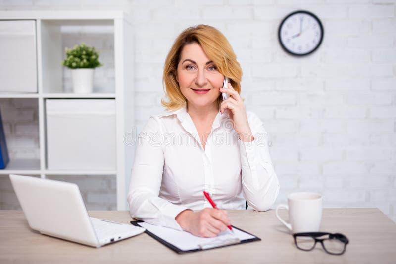 Жизнерадостная зрелая бизнес-леди сидя в офисе, говоря по телефону и писать что-то на доске сзажимом для бумаги стоковая фотография