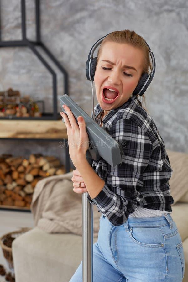Жизнерадостная молодая женщина наслаждаясь запевом поя с пылесосом пока убирающ дом стоковые изображения rf