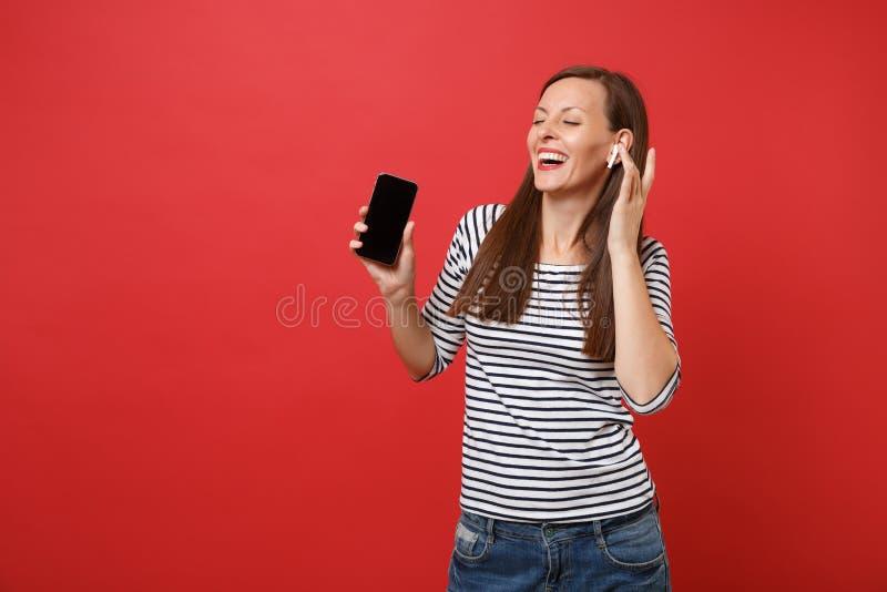 Жизнерадостная молодая женщина с беспроводными наушниками держит мобильный телефон с музыкой пустого черного пустого экрана слуша стоковое изображение rf