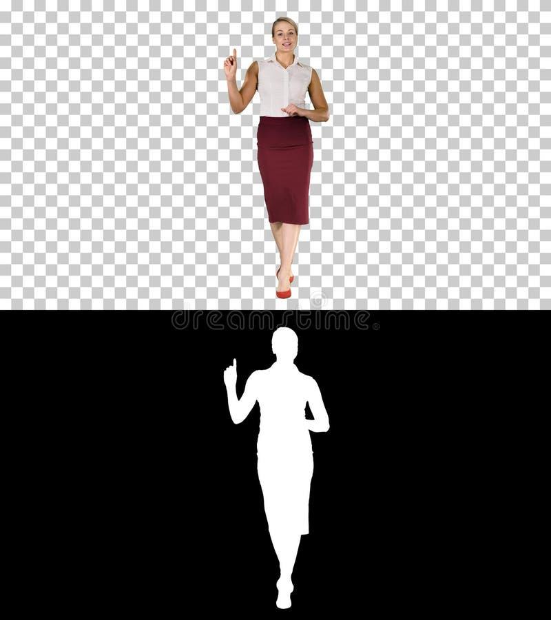 Жизнерадостная молодая красивая женщина в официальных одеждах идя, говоря к камере и указывая на сторону, канал альфы стоковые фото