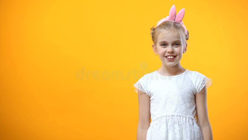 Жизнерадостная девушка в держателе ушей зайчика усмехаясь, изолированная на оранжевой предпосылке стоковая фотография rf