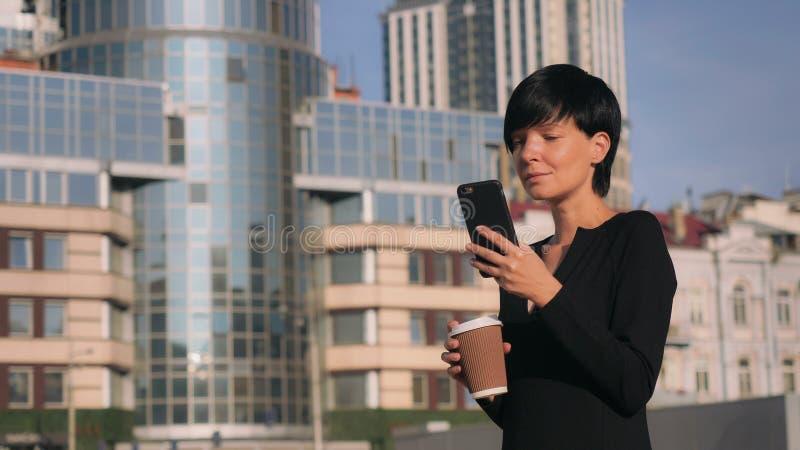 Жизнерадостная девушка наслаждается смартфоном пользы кофе outdoors стоковое фото rf