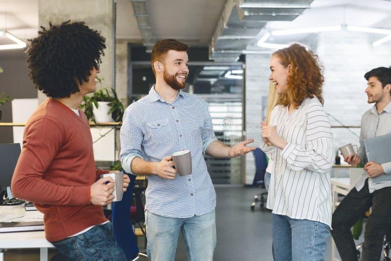 Жизнерадостные коллеги наслаждаясь перерывом на чашку кофе в офисе стоковое изображение