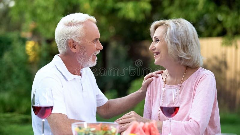 Жизнерадостные старшие пары имея романтичную дату в задворк, встречая вебсайт стоковое изображение