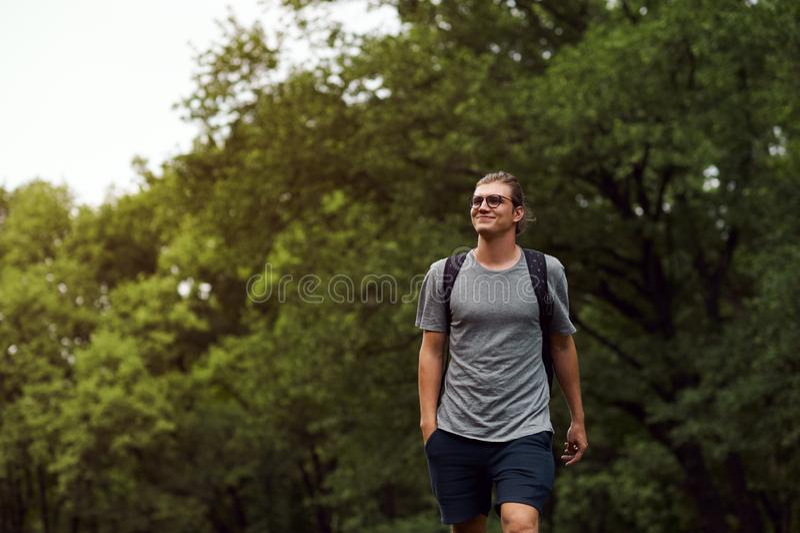 Жизнерадостный привлекательный молодой студент с bagpack, усмехающся и имеющ полезного время работы пока идущ публично парк Краси стоковая фотография rf