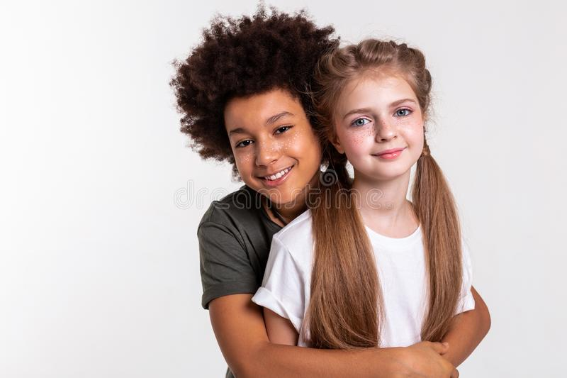 Жизнерадостный темн-с волосами мальчик плотно обнимая его друга стоковая фотография rf