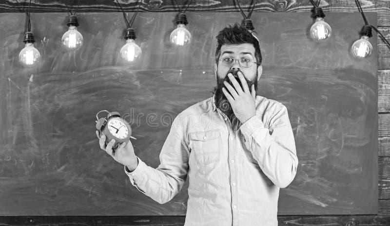 Забыл о концепции времени Человек с бородой и усик на сотрясенной стороне в классе Бородатый битник держит часы стоковое изображение