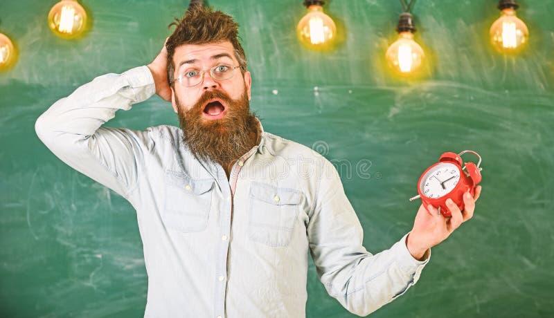 Забыл о концепции времени Человек с бородой и усик на confused выражении стороны в классе Портрет занятого стоковые фото