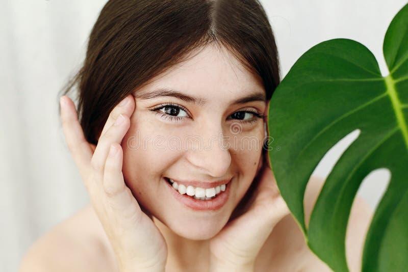 Забота и обработка кожи глаза Портрет красивой молодой счастливой женщины держа руки на коже глаз на зеленых лист ладони Наслажда стоковая фотография rf