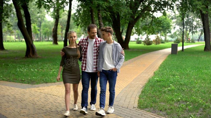 Заботя отец идя с подростковыми детьми в парке, outdoors выходных семьи стоковое изображение rf