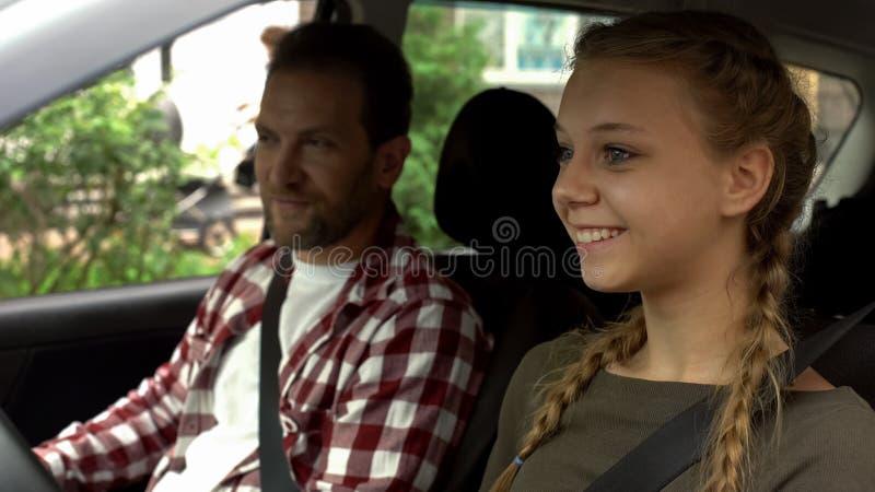 Заботя отец уча, что молодая дочь управляла автомобилем, новой управляя школой стоковые фотографии rf
