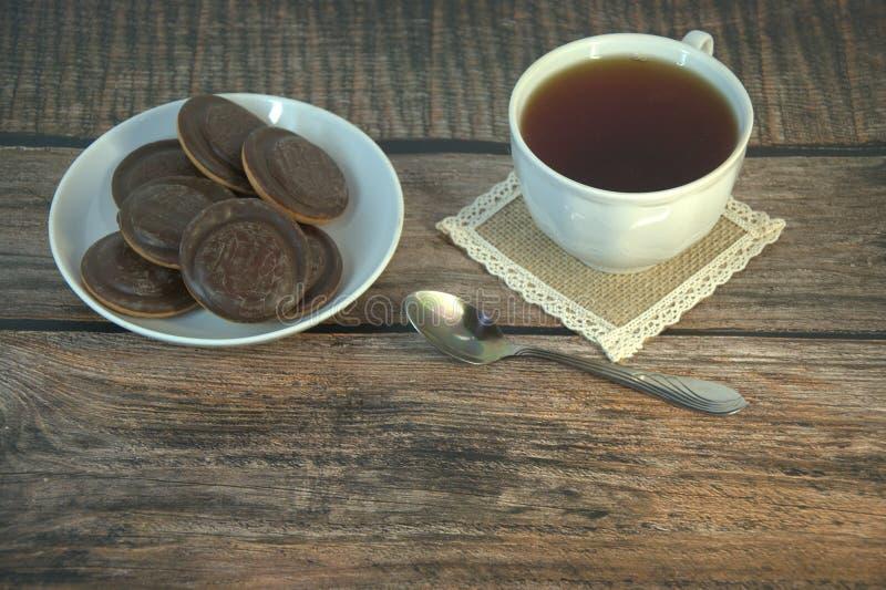 Завтрак, чашка чаю и печенья печенья с замороженностью шоколада на чашке фарфора и ложке, лож на деревянном столе стоковое фото rf