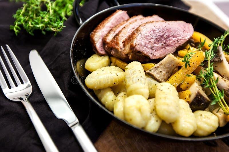 Зажаренная в духовке утка с грушей, marinated в красном вине с gnocchi и устрицами стоковое изображение