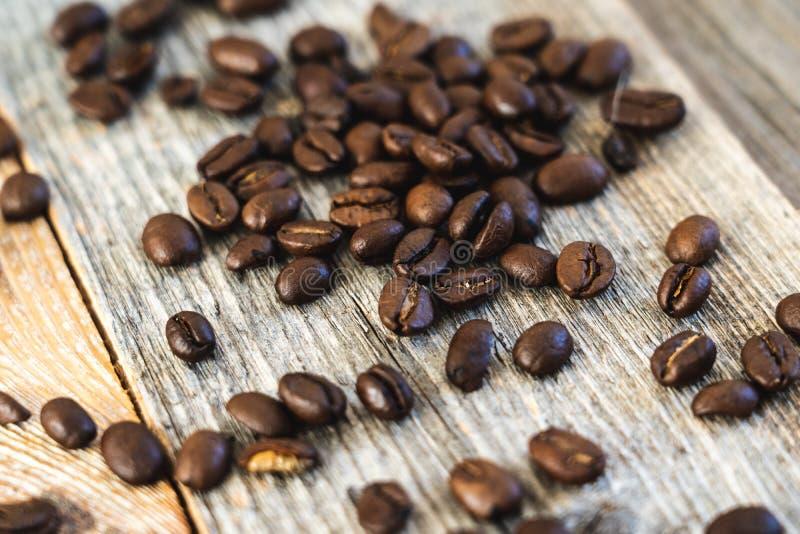Зажаренные в духовке кофейные зерна на деревенских деревянных досках стоковая фотография