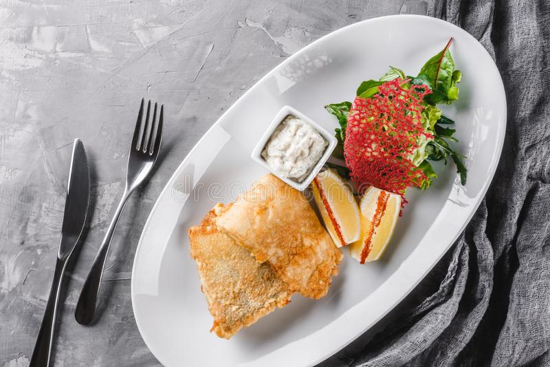 Зажаренное филе рыб с салатом и лимоном в плите над деревенской предпосылкой рыбы тарелки горячие Взгляд сверху, плоское положени стоковая фотография