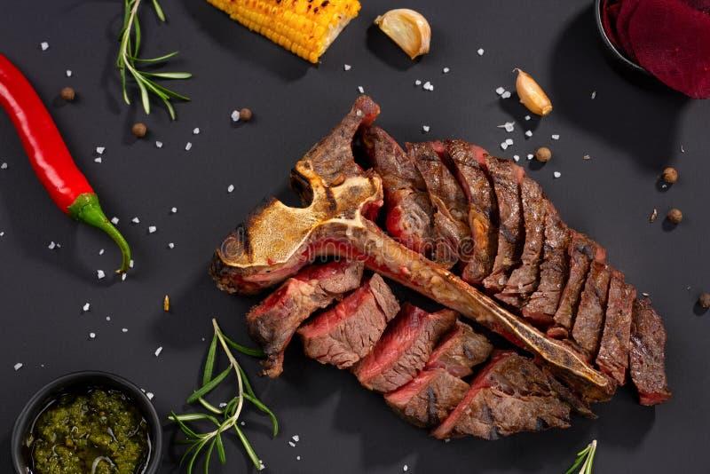 Зажаренное отрезанное мясо на деревенской черной предпосылке Зажаренный стейк на косточке, сервировка ресторана с специями и трав стоковая фотография