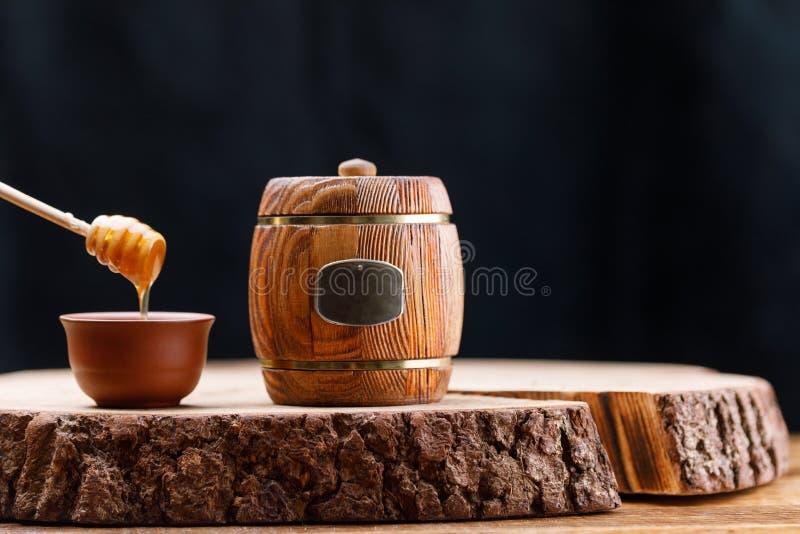 Закрытый деревянный бочонок с медом и ложкой меда на деревянной пиле на темной предпосылке barrette Конец-вверх стоковые фото