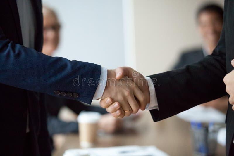 Закройте вверх исполнительных бизнесменов в костюмах мужские руки трясут стоковая фотография