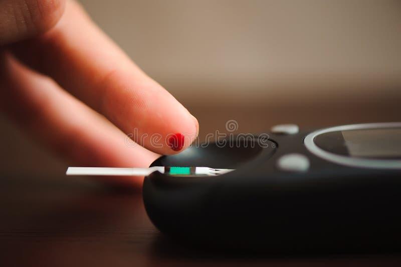 Закройте вверх мужского пальца с нашивкой падения и теста крови к проверке уровня сахара в крови метром глюкозы стоковые изображения