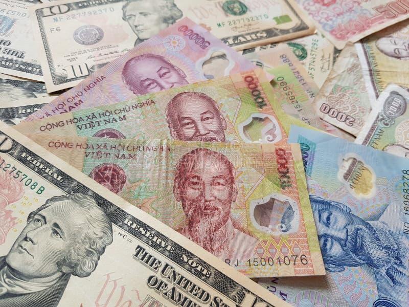 Закройте вверх по банкнотам вьетнамца с Хо Ши Мин доллар портрета и Соединенных Штатов темпы роста девизов в долларах принципиаль стоковые изображения
