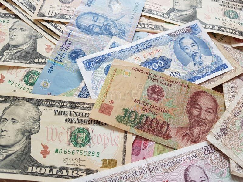 Закройте вверх по банкнотам вьетнамца с Хо Ши Мин доллар портрета и Соединенных Штатов темпы роста девизов в долларах принципиаль стоковое изображение