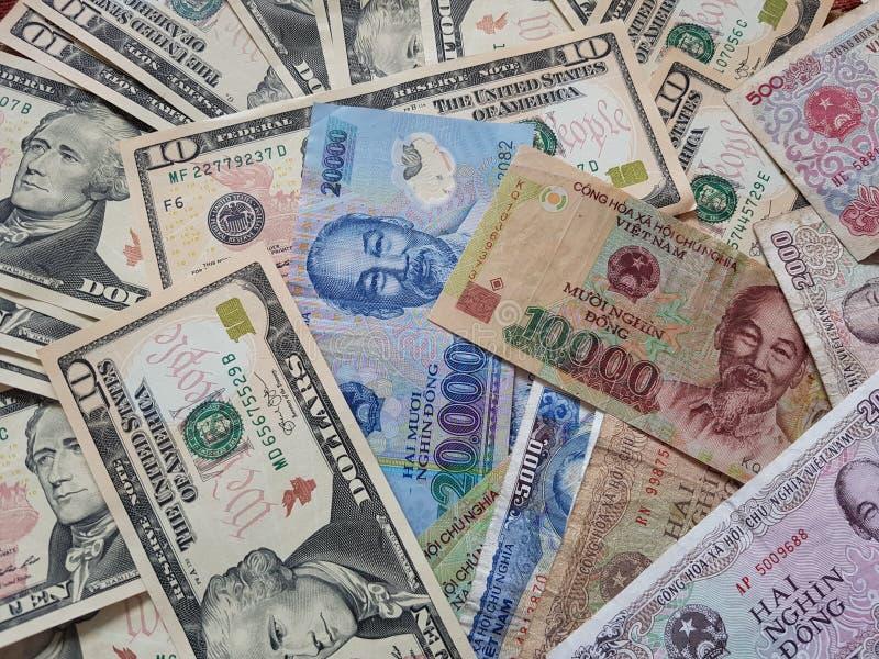 Закройте вверх по банкнотам вьетнамца с Хо Ши Мин доллар портрета и Соединенных Штатов темпы роста девизов в долларах принципиаль стоковая фотография