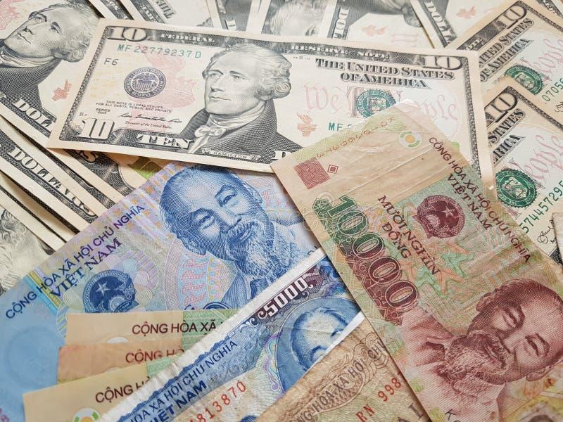 Закройте вверх по банкнотам вьетнамца с Хо Ши Мин доллар портрета и Соединенных Штатов темпы роста девизов в долларах принципиаль стоковое фото rf