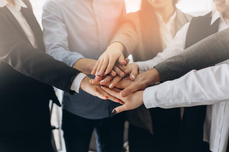 Закройте вверх по взгляд сверху молодых бизнесменов кладя их руки совместно Стог рук Единство и концепция сыгранности стоковые фото