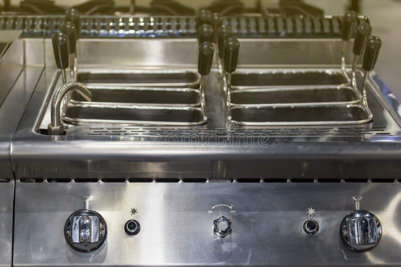 Закройте вверх по современному управления бака fryer газа глубокого и шкалы ручки с нержавеющей корзиной для промышленной еды стоковое изображение