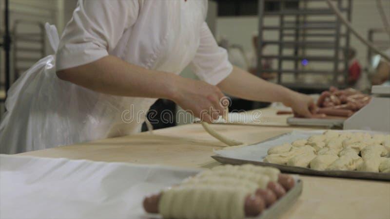 Закройте вверх для женщины создавая программу-оболочку сосиски в сырцовом печенье слойки на пекарне Сырцовые хот-доги свернули в  стоковое изображение rf