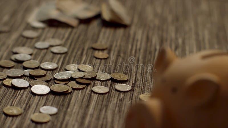 Закройте вверх для копилки с монетками падая на старом деревянном столе, сохраняющ концепцию денег Розовое moneybox с много монет стоковое фото rf