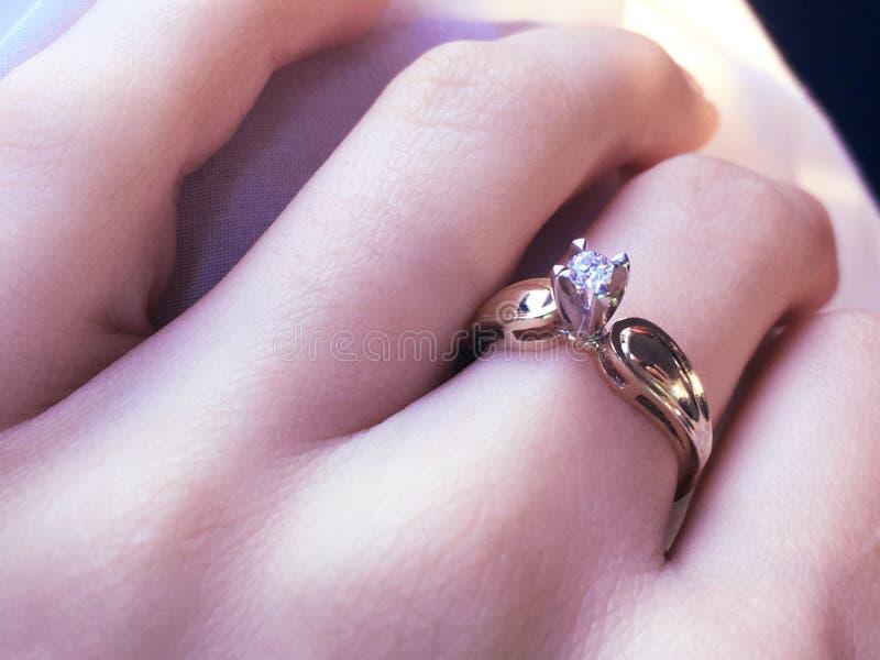 Закройте вверх элегантного кольца с бриллиантом на пальце с серой предпосылкой шарфа Кольцо диаманта стоковое фото