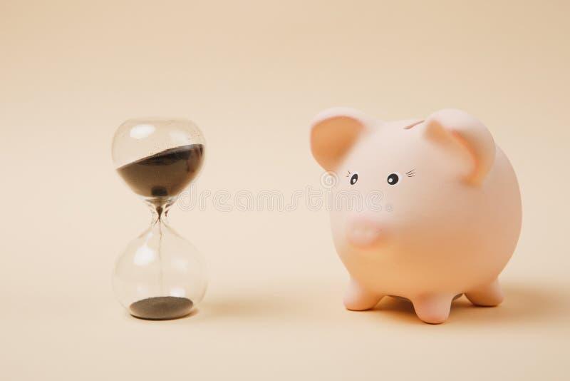 Закройте вверх розовых piggy банка и sandglass денег на пастельной бежевой предпосылке стены Накопление денег, вклад стоковая фотография