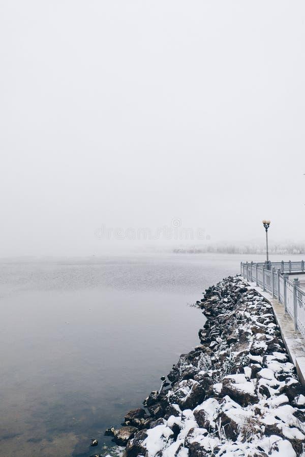 Замороженные камни около озера в зимнем дне туманнейше стоковое фото rf