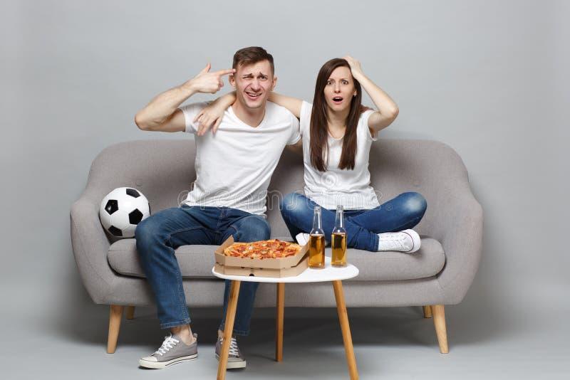 Заниманные футбольные болельщики человека женщины пар веселят вверх пальцы пункта команды поддержки любимые к голове если он окол стоковые фотографии rf