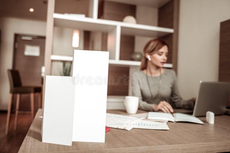 Занятая трудолюбивая женщина сидя на таблице с документами стоковое фото