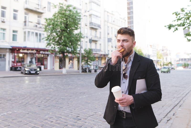 Занятый человек готовит дорогу, ел сэндвич, выпивая кофе и улавливать такси стоковые фото