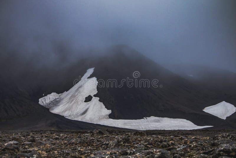 Заплата снега выглядит как голова чужеземца в гористых местностях Исландии стоковое фото