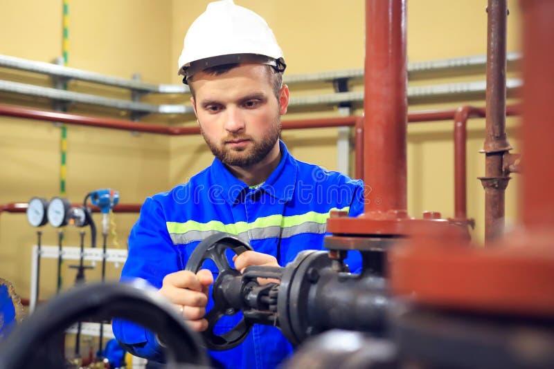 Запорная заслонка работника поворачивая на трубе боилера стоковые изображения