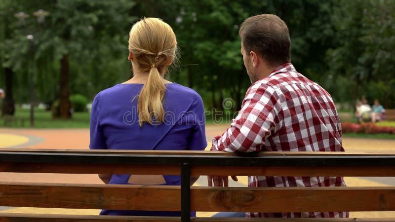 Задний взгляд пар сидя на скамейке в парке, времени траты совместно, разговор стоковая фотография rf