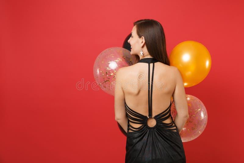 Задний вид сзади молодой женщины в черном платье смотря в сторону праздновать воздушных шаров удерживания изолированный на красно стоковое изображение