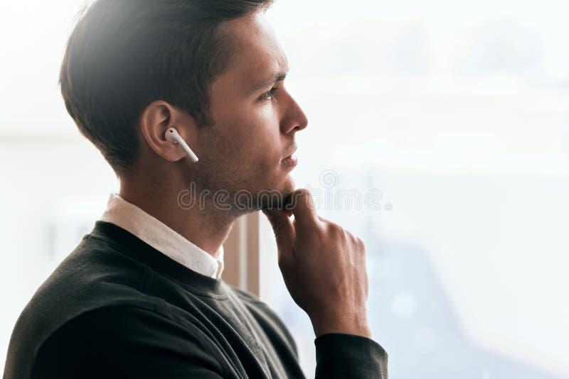 Задумчивый молодой красивый человек имеет звонок с коллегой и смотреть через окно в офисе, говоря от беспроводных наушников стоковые фотографии rf