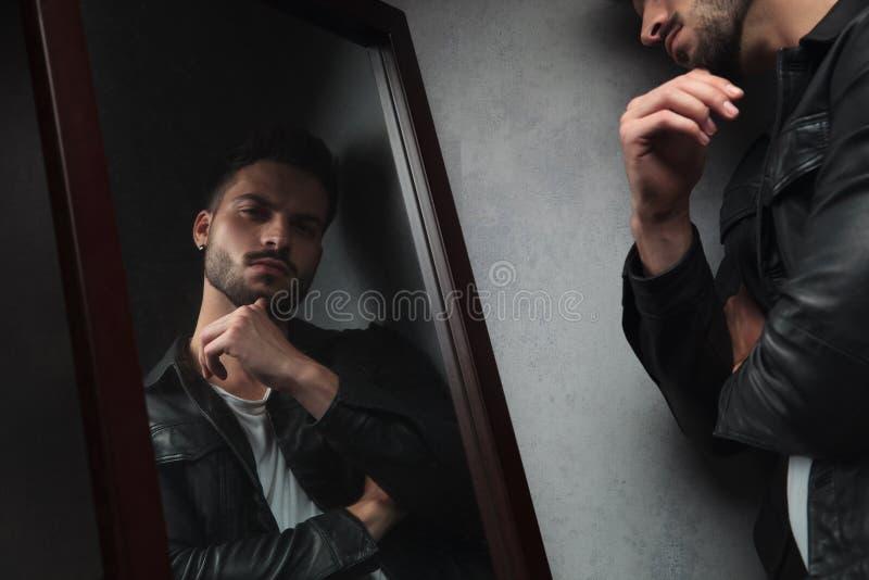 Задумчивый молодой человек смотрит в зеркале стоковая фотография
