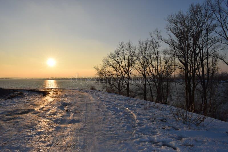 Заснеженная дорога, ведущая к реке Волге. Sunset beach on a river Volga with snow road royalty free stock images