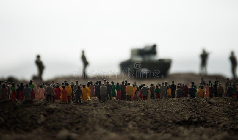 Захваченный враждебной концепцией Военные силуэты и толпа на предпосылке неба тумана войны Солдаты и бронированные транспортные с стоковое фото