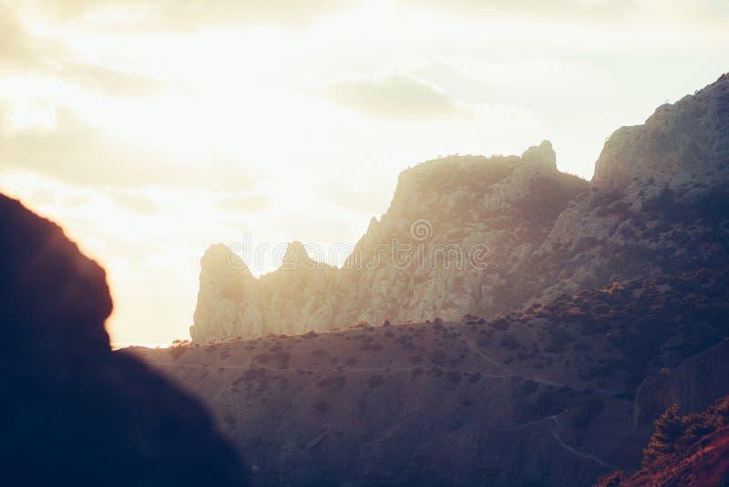 Заход солнца в горах внутри освещает контржурным светом Крым, деревня Novyi Svet стоковая фотография